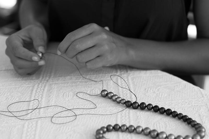 Expert hands crafting a necklace
